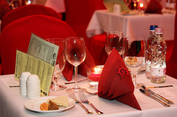 table with red napkins set for a romantic meal