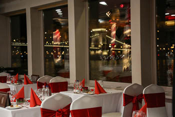 dinne rtables set in white-red decor on a panorama boat at night