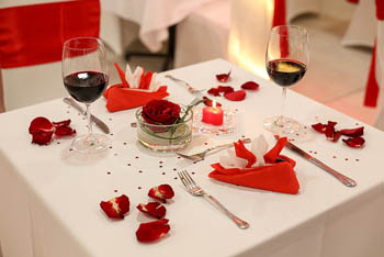 a small square table set with white cloth and red napkins, and red rose petals