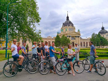 bikers on a tour in the City Park, in front of the Szechenyi Bath on a slightly cloudy but warm day
