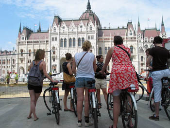 tourists on a bike tour standing in front of the Parliament building on a hot summer day