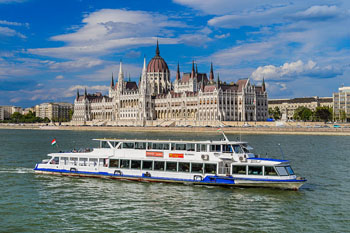 a white sightseeing boat in front of the Parliament