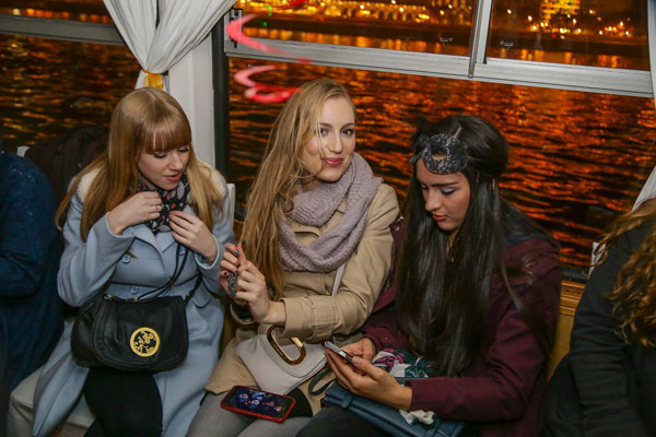 3 girls sitting in front of a panorama window of the cruise boat