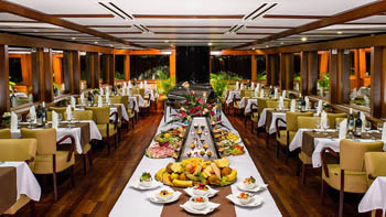 white clothed tables set for dinner in a ship's restaurant