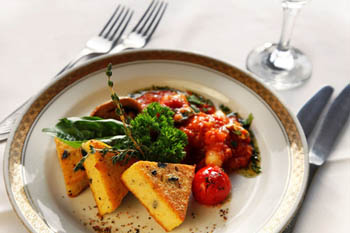3 triangle-shaped grilled polenta pieces with a ragout on a golden trimmed round white plate