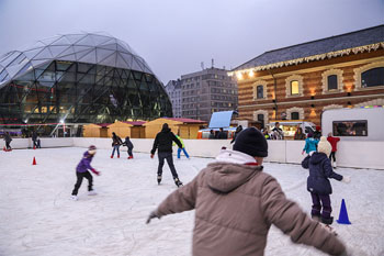 a couple of ice skaters on the rink in front of the Balna