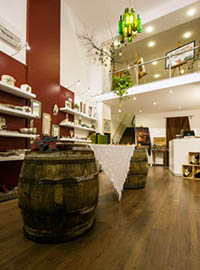 2 wooden barrels, shelves with ceramics bottle sof wine on shelves in the shop