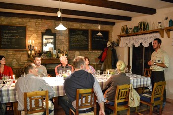 7 people sitting at the dinner table in a cellar and lisetning to Tomi Hernyák