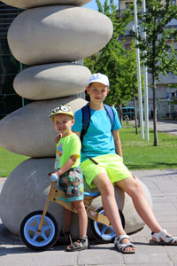 our two boys at a monument of giant pebbles in millenaris park