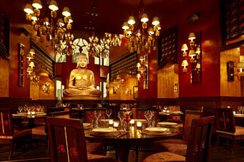 slightly dark interior of the restaurant with lots of lamps and a large Buddha statue in the background