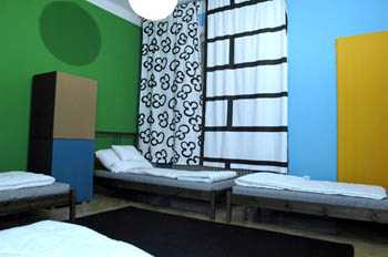 a green and blue bedroom with single and and a double bed