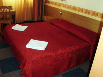 a twin bed covered with a red bedcover