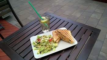 toasted sandwich and salad on a plate on a square wooden table