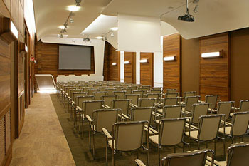 rows of chairs i the wood-paneled conference room