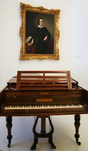 an old cherry wood piano with Franz Liszt's painting onthe wall behind it