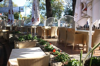 garden of the restaurant with rattan chairs and tables in the afetrnoon