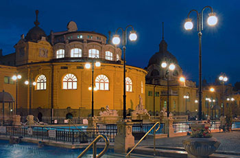 bathers enjoying the open air pools at the blue hour, the lights on inside the yeloow bath building