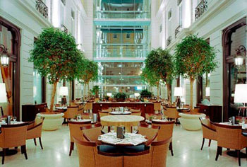 tables and chairs, green plants in the light atrium of Corinthia