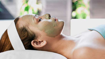 a green mud mask on a young lady's face