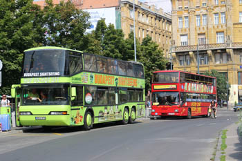 a lime green and a red double decker tour bus in the city center