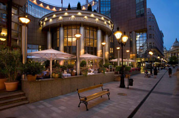 street view of the Kempinski Corvinus hotel at dusk with the lights on