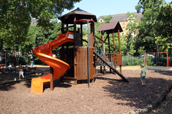 a wooden castle with a red slide on Klauzal playground