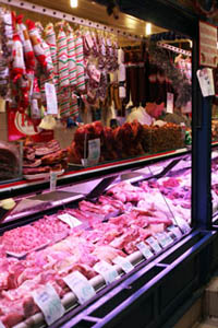 a meat counter with sausages and salamis hanging