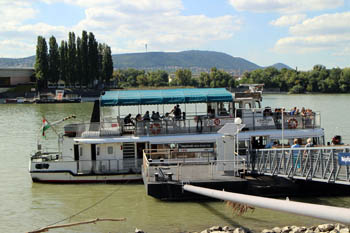 green and white public boat tour in a port on the Danube