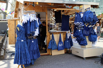 blue folk dresses a a wooden stall