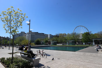 , the Eye Ferris wheel and some people sitting on benches around the lake in Erzsenet Square park