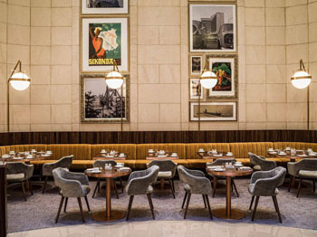 The Kupola lounge with round tables and grey plush chairs, historic photos, posters on the wall