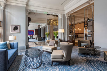 modern lobby of the Ritz Carlton Bp with blue-grey carpet, blue sofa, beige armchairs