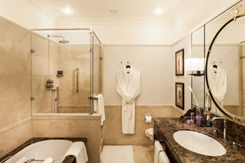 bathroom in one of the hotel rooms with beige and golden-hued tiles and counter
