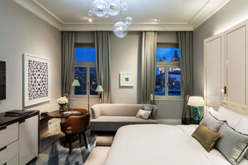 one of the Deluxe rooms with a King size bed, sofa, desk and two windows