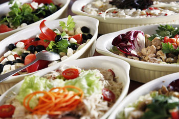 various salads in white oval bowls