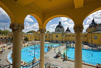 view of the outdoor pools and the yellow bath building through an arcade