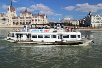a white boat plighing the Danube at the Parliament