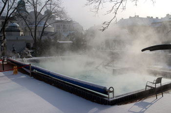 steam over the outdoor hot pool of the Gellert Spa
