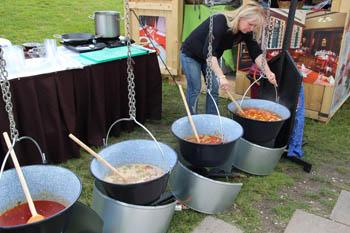 cooking stew in kettles over open fire in Millenaris park