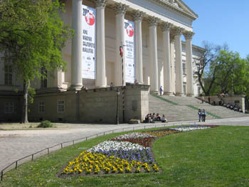 the colonnaded front of the National Museum with a colorful flower bed in the foreground