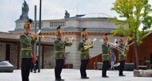 brass band in green and red hussar uniform