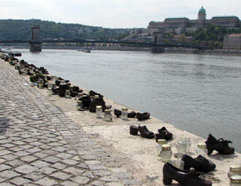 pairs of cast iron shoes on the Danube ban kwith flowers and candles around them