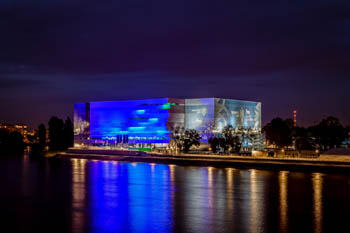 the facad eof the Arena light painted in blue at night