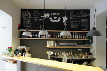 the bar of Lumen cafe with a large, square black board on the wall