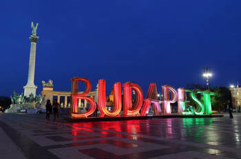 "installation of the word ""Budapest"" in the red, white and green, at Millenial monument in the background"
