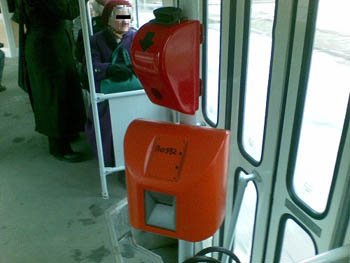 a red punch machine and an orange ticket validation machine under it on a bus