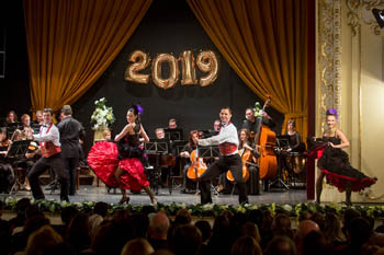 a gypsy string orchestra on stage, 2019 in golden balloons in the background