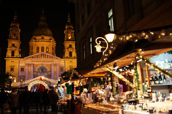 wooden Christmas market stall with the Basilica in the background at night