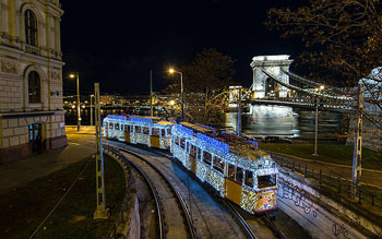 tram 47 decked out in strings of white LED light, the Chain bridge in the background at night