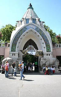 The arched gate of the zoo with a stone elephant statue at each side